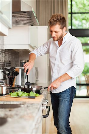 stove - Smiling man cooking in kitchen Stock Photo - Premium Royalty-Free, Code: 649-06040115