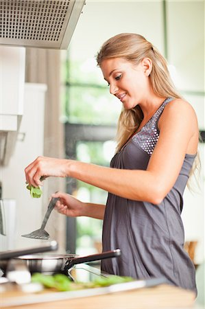 stove - Smiling woman cooking in kitchen Stock Photo - Premium Royalty-Free, Code: 649-06040117