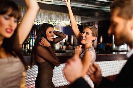 Smiling friends dancing in bar Stock Photo - Premium Royalty-Free, Code: 649-06040175