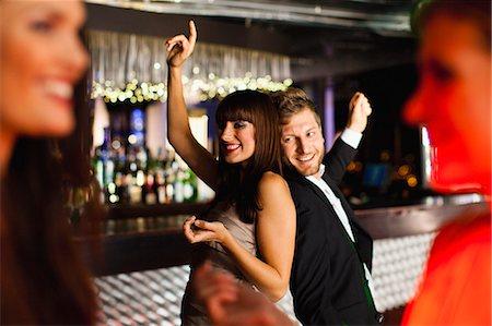 Smiling friends dancing in bar Stock Photo - Premium Royalty-Free, Code: 649-06040178