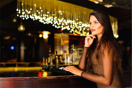 Smiling woman standing at bar Stock Photo - Premium Royalty-Free, Code: 649-06040179