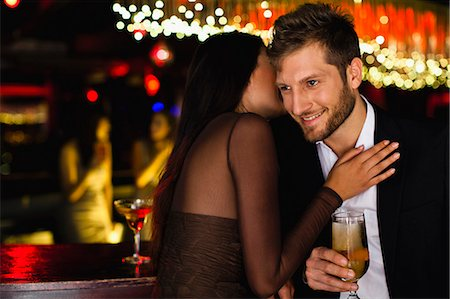 flirting - Smiling couple whispering at bar Stock Photo - Premium Royalty-Free, Code: 649-06040185