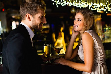 flirting - Smiling couple having drinks at bar Stock Photo - Premium Royalty-Free, Code: 649-06040182