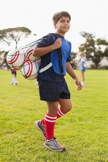 Boy carrying soccer balls on pitch Stock Photo - Premium Royalty-Free, Image code: 649-06040279