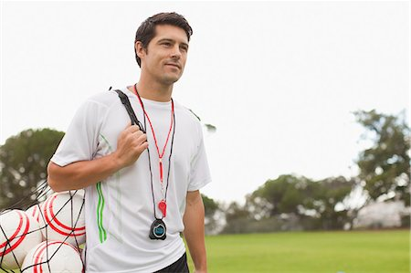 stop watch - Coach carrying soccer balls on pitch Stock Photo - Premium Royalty-Free, Code: 649-06040285