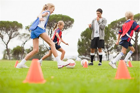 female playing soccer - Coach training childrens soccer team Stock Photo - Premium Royalty-Free, Code: 649-06040287