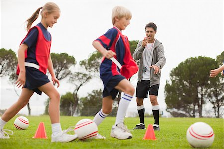 female playing soccer - Coach training childrens soccer team Stock Photo - Premium Royalty-Free, Code: 649-06040289
