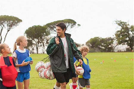 Coach carrying soccer balls on pitch Stock Photo - Premium Royalty-Free, Code: 649-06040281