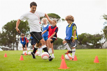 female playing soccer - Coach training childrens soccer team Stock Photo - Premium Royalty-Free, Code: 649-06040295