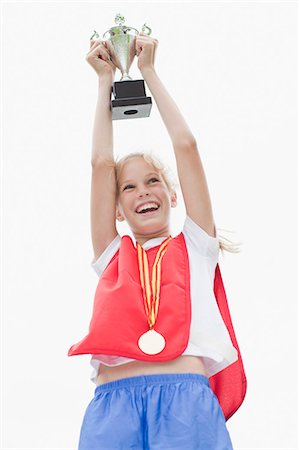 preteen girl - Smiling girl holding trophy Stock Photo - Premium Royalty-Free, Code: 649-06040322