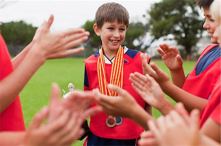Children cheering teammate with trophy Stock Photo - Premium Royalty-Free, Code: 649-06040323