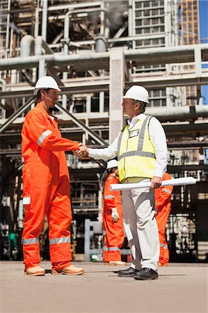 refinery - Workers shaking hands at oil refinery Stock Photo - Premium Royalty-Free, Code: 649-06040357