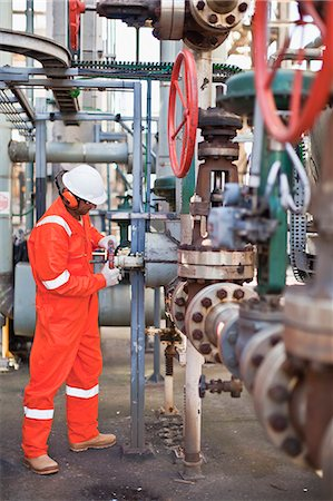 refinery - Worker adjusting gauge at oil refinery Stock Photo - Premium Royalty-Free, Code: 649-06040402