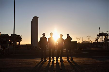 Silhouette of workers at oil refinery Stock Photo - Premium Royalty-Free, Code: 649-06040426
