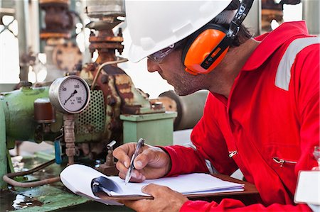 refinery - Worker noting gauge at oil refinery Stock Photo - Premium Royalty-Free, Code: 649-06040468