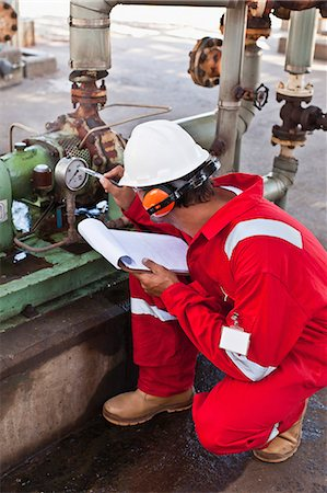 refinery - Worker noting gauge at oil refinery Stock Photo - Premium Royalty-Free, Code: 649-06040469