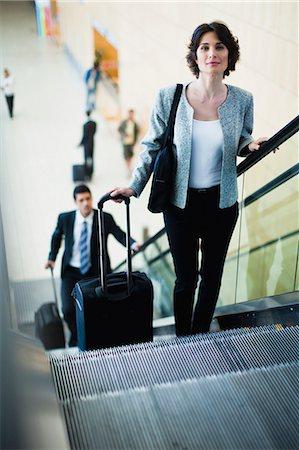 Businesswoman riding escalator Stock Photo - Premium Royalty-Free, Code: 649-06040643