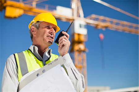 Worker using walkie talkie on site Stock Photo - Premium Royalty-Free, Code: 649-06040716