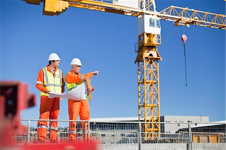 Workers reading blueprints on site Stock Photo - Premium Royalty-Free, Code: 649-06040712