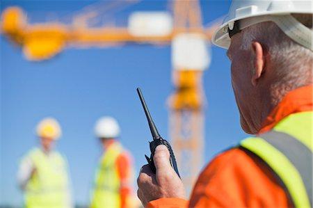 Worker using walkie talkie on site Stock Photo - Premium Royalty-Free, Code: 649-06040720