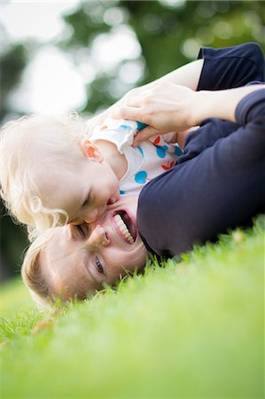 daughter kissing mother - Mother and baby playing in grass Stock Photo - Premium Royalty-Free, Code: 649-06040816