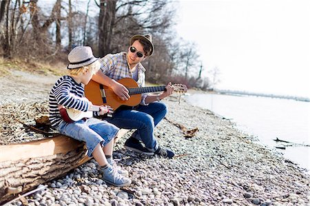 Father and son playing guitars by creek Stock Photo - Premium Royalty-Free, Code: 649-06040818