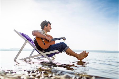 Man relaxing in lawn chair in creek Stock Photo - Premium Royalty-Free, Code: 649-06040827