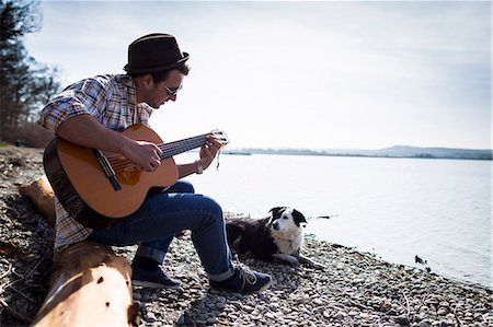 dogs in nature - Man playing guitar with dog by creek Stock Photo - Premium Royalty-Free, Code: 649-06040820
