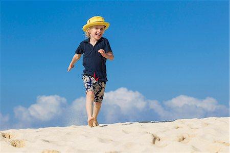 Boy walking on sandy beach Stock Photo - Premium Royalty-Free, Code: 649-06040837