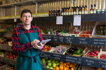 Grocer using tablet computer in store Stock Photo - Premium Royalty-Free, Code: 649-06041012