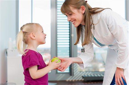 Doctor handing girl an apple in office Stock Photo - Premium Royalty-Free, Code: 649-06041115
