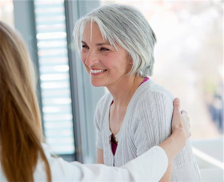 Doctor hugging smiling woman in office Stock Photo - Premium Royalty-Free, Code: 649-06041127