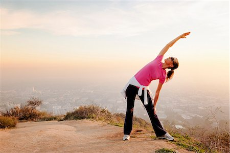 standing - Woman stretching on hilltop Stock Photo - Premium Royalty-Free, Code: 649-06041488