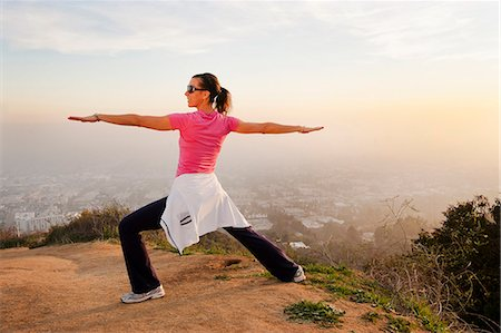 standing - Woman stretching on hilltop Stock Photo - Premium Royalty-Free, Code: 649-06041489