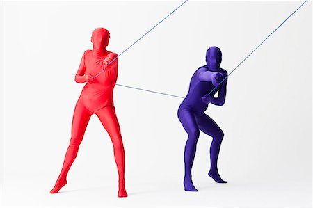 pulling - Couple in bodysuits playing with string Stock Photo - Premium Royalty-Free, Code: 649-06041694