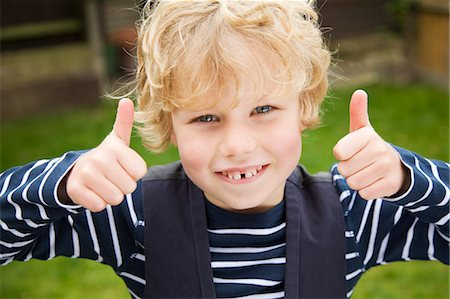 Smiling boy giving thumbs-up outdoors Stock Photo - Premium Royalty-Free, Code: 649-06041770