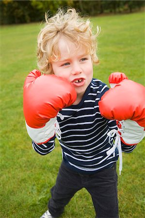 Boy playing with boxing gloves outdoors Stock Photo - Premium Royalty-Free, Code: 649-06041781