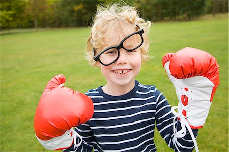 Boy playing with boxing gloves outdoors Stock Photo - Premium Royalty-Free, Code: 649-06041783