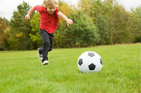 recreational pursuit - Boy playing with soccer ball in field Stock Photo - Premium Royalty-Free, Code: 649-06041799