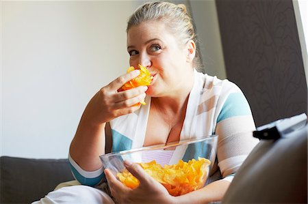 fat lady sitting - Smiling woman eating chips on sofa Stock Photo - Premium Royalty-Free, Code: 649-06041829