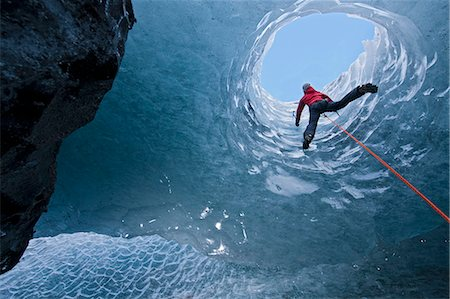 Climber climbing out of ice cave Stock Photo - Premium Royalty-Free, Code: 649-06041880