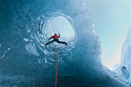 Climber climbing out of ice cave Stock Photo - Premium Royalty-Free, Code: 649-06041881