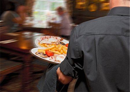 Waiter carrying plates in restaurant Stock Photo - Premium Royalty-Free, Code: 649-06041916