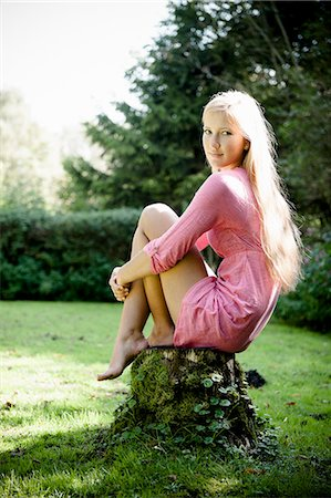Woman sitting on stump outdoors Stock Photo - Premium Royalty-Free, Code: 649-06112535