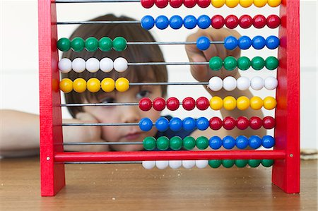Boy playing with abacus Stock Photo - Premium Royalty-Free, Code: 649-06112570
