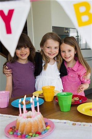 Smiling girls hugging at birthday party Stock Photo - Premium Royalty-Free, Code: 649-06112593