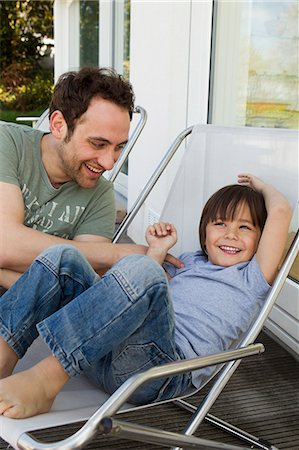 Father and son playing in deck chairs Stock Photo - Premium Royalty-Free, Code: 649-06112608