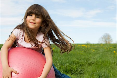 Girl playing on bouncy ball in field Stock Photo - Premium Royalty-Free, Code: 649-06112622