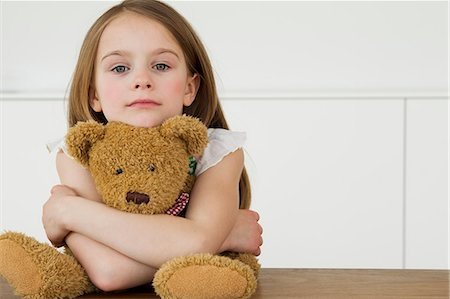 Girl hugging teddy bear at table Stock Photo - Premium Royalty-Free, Code: 649-06112633