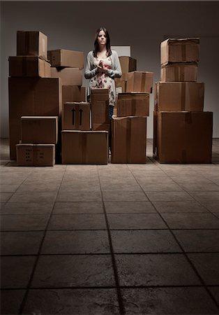 Teenage girl in pile of cardboard boxes Stock Photo - Premium Royalty-Free, Code: 649-06112641